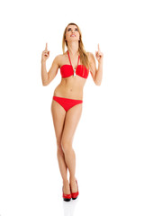 Woman in a swimsuit pointing on copy space