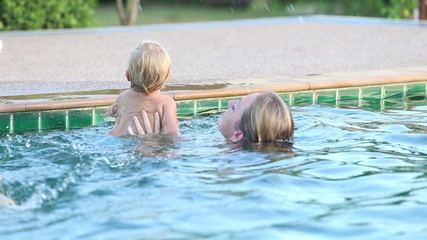 child enjoy swimming in the pool with his mother