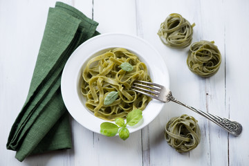Tagliatelle with green basil in a glass plate, high angle view