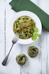 Above view of tagliatelle with pesto in a glass plate, close-up