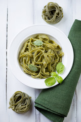Tagliatelle with basil over white wooden background, above view