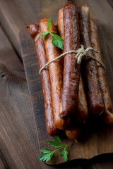 Stack of smoked sausages with parsley on a rustic chopping board