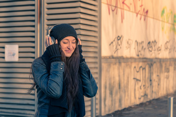 Beautiful young woman listening to music in the city streets