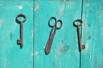 two antique metal key and rusty scissors on wall
