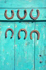 six antique rusty horseshoe on  green wooden farm barn door