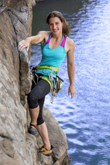 Smiling female climber over the river