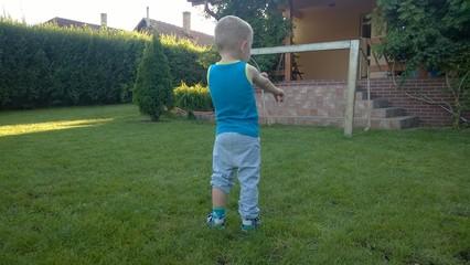 kleiner Junge spielt auf der Wiese hinterm Haus