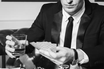 A young man in a business suit sitting at the poker table