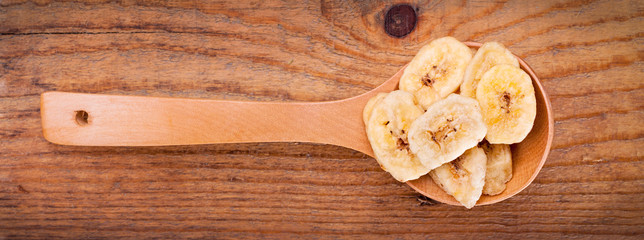 Dried banana chips in wooden spoon