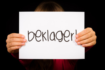 Child holding sign with Norwegian word Beklager - Sorry
