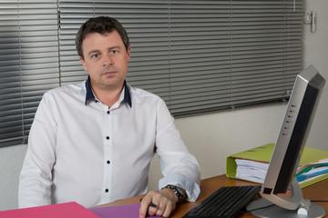 Homme à son bureau stylo dans les doigt regard franc