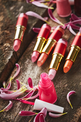 Lipsticks with nail polish and flower petals