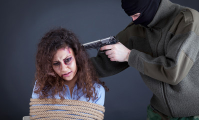 terrorists threatening the a frightened girl with gun