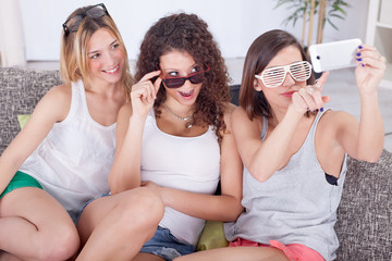 portrait of three friends taking photos with a smartphone