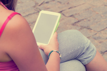 Girl typing messages on her smartphone/tablet.
