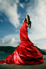 beautiful young woman in red long dress outdoor