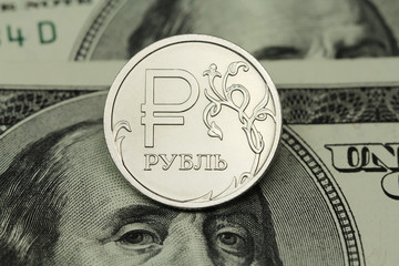 coin one ruble on a background of US dollars