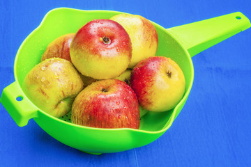 Red apples in green sieve on blue