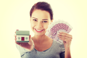 Young woman with money and house.