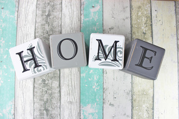 Home sign on a distressed wood background with turquoise tones.