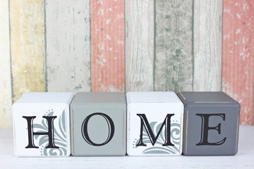 Blocks spelling Home on a distressed wood background.