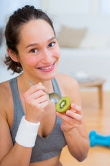Attractive sportive woman eating kiwi after sport