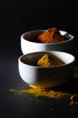Spices in cups on a black background