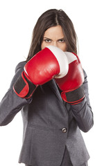 angry business woman with boxing gloves on a white background