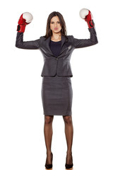 Serious business woman with boxing gloves in winning position