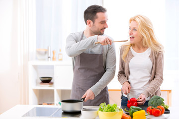 Young attractive man give food to his wife to taste