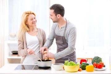 Young attractive man helping out his wife while cooking