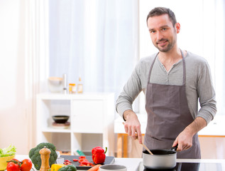 Young attractive man cooking in a kitchen