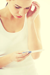 Worried woman holding pregnancy test.