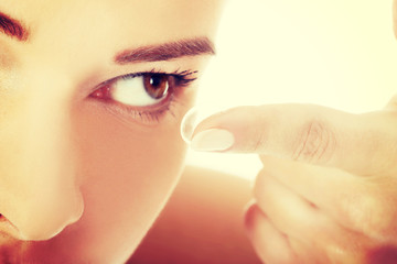 Woman putting lens into eye.