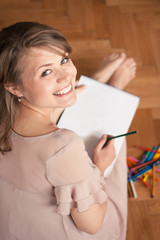 Let's draw: young woman sitting on the floor with a notebook on