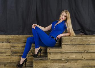 Beautiful slim blonde in blue overalls