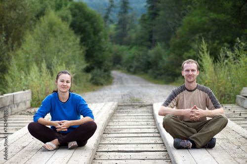 canvas print picture Tourist couple sitting on a wooden bridge