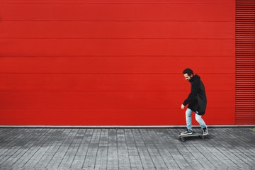 Guy rides his skate in front of red wall