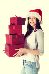 Young santa woman holding stack of presents.