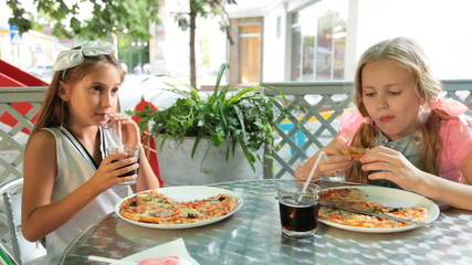 Little girls eating pizza and drinking cola drink