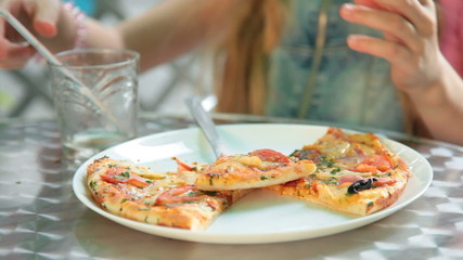 Eating pizza at outdoor cafe closeup