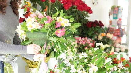 Woman making bunch of flowers in a flower shop