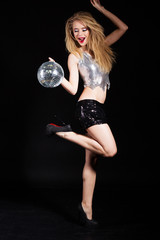 Fashion girl with disco ball over black background