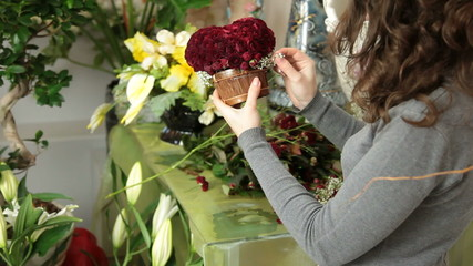 Woman making a flower arrangement of red roses