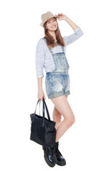 Young fashion girl in jeans overalls and hat posing isolated