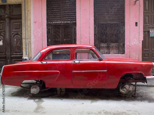Fotobehang Vintage cars Vieille voiture rouge sur cales à Cuba.