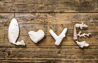 Love.Shells letters on vintage wood background.Beach concept.