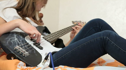 Teen Girl Playing Bass Guitar At Home