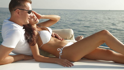 Adult couple enjoying summer vacation on deck of yacht