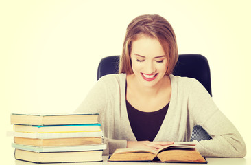 Student woman sitting by the desk with books.